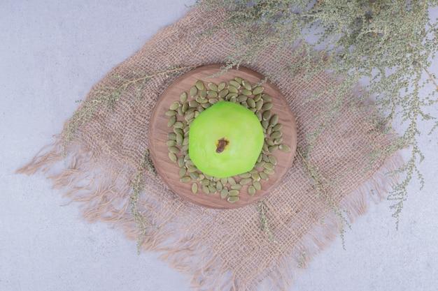 Une poire verte sur une planche de bois avec des graines de citrouille
