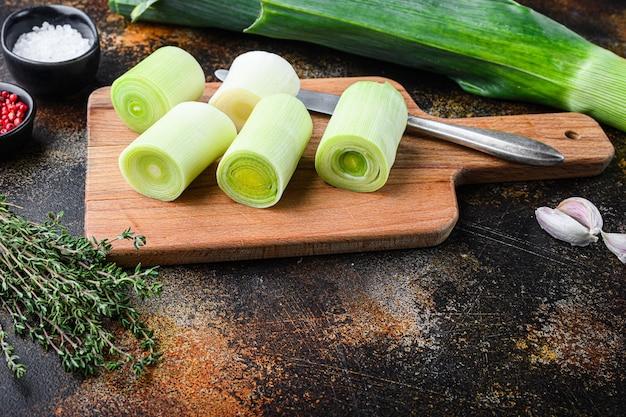 Poireaux hachés biologiques pour la cuisson des poireaux braisés sur planche de bois avec des ingrédients d'herbes , sur fond de métal rustique sombre, vue latérale.