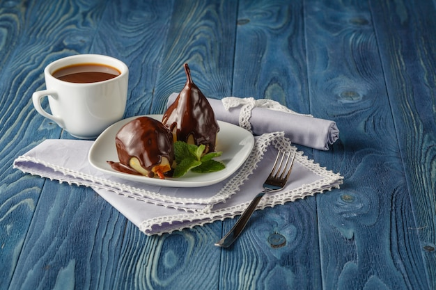 Poires au sirop de caramel à la menthe sur une plaque blanche avec du chocolat en arrière-plan sur un fond sombre