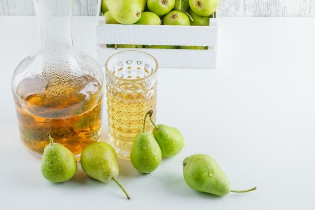 Poires avec boisson dans une boîte en bois sur mur blanc et grungy, high angle view.