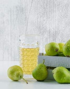 Poires avec boisson dans une boîte en bois sur mur blanc et grungy, vue latérale.