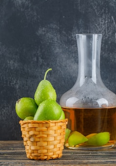 Poires dans un panier avec vue de côté de boisson au cidre sur mur en bois et grungy