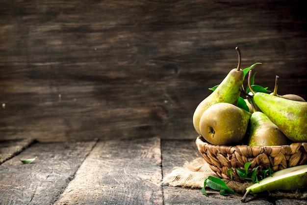 Poires fraîches dans un panier sur table en bois.