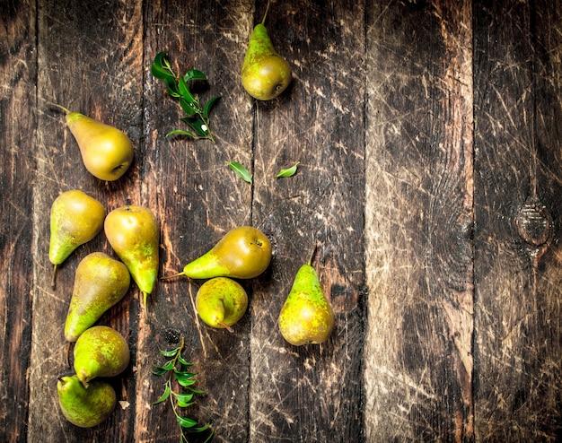 Poires fraîches avec des feuilles sur table en bois.