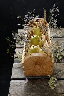 Poires fraîches et fleurs des champs dans une boîte en bois sur la vieille table en bois