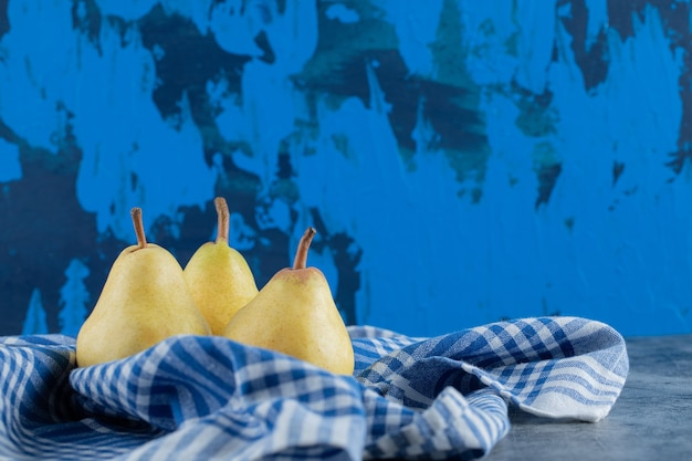 Poires jaunes juteuses sur un torchon à carreaux bleus