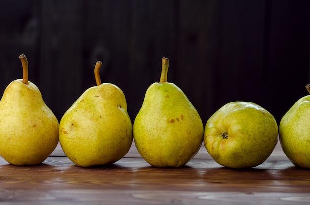 Poires jaunes mûres sur fond rustique en bois. fruits d'été, récolte.