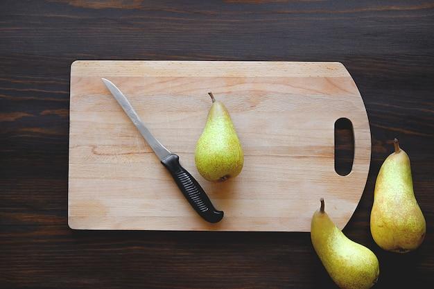Poires jaunes et vertes mûres, fraîches et entières, couteau de cuisine et planche à découper