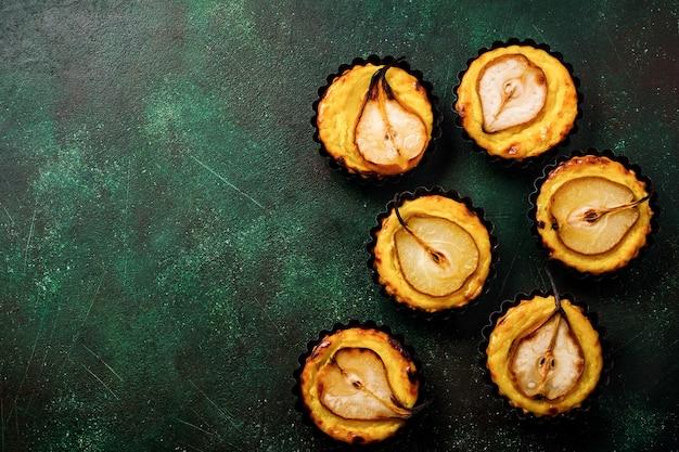 Poires et mini tartelettes à la crème sur une vieille table en béton vert foncé