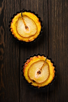 Poires et mini tartelettes à la crème sur une vieille table en bois brun foncé