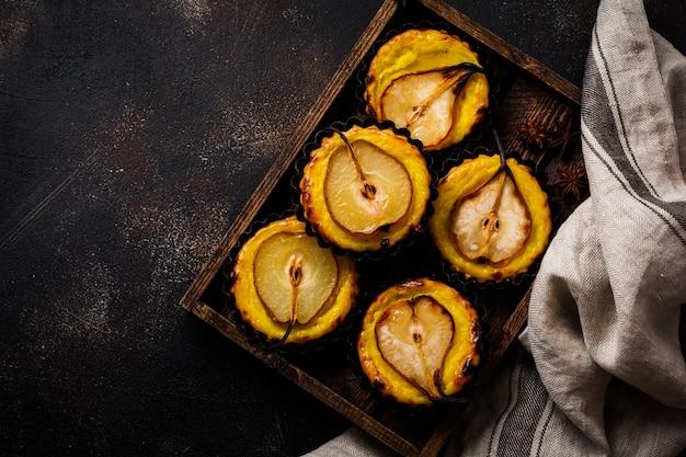 Poires et mini tartes à la crème sur un vieux fond de table en béton brun foncé. vue de dessus.