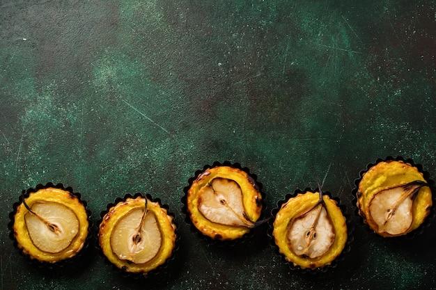 Poires et mini tartes à la crème sur un vieux fond de table en béton vert foncé. vue de dessus.