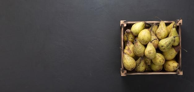 Poires mûres dans une caisse en bois sur table en béton