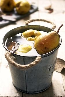 Poires mûres et feuilles de poirier dans un seau en fer avec de l'eau et sur une table en bois. style rustique.