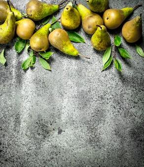 Poires mûres avec des feuilles sur table rustique.