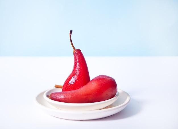Poires pochées au vin rouge aux épices sur fond blanc