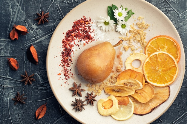 Poires pochées aux épices au sirop sur la plaque blanche décorée de fruits. délicieux dessert pour les vacances.
