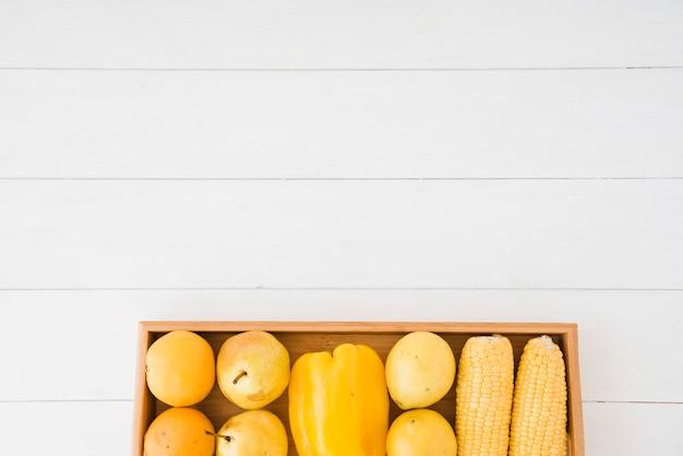 Poires; poivron et maïs sur un plateau en bois au-dessus de la table blanche