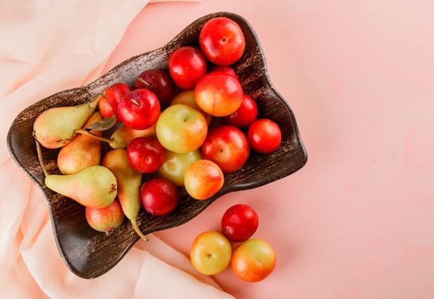 Poires et prunes dans une assiette sur une surface rose et textile