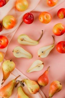 Poires et prunes sur surface rose et textile