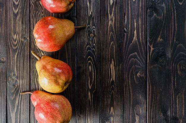 Poires rouge-jaune vif dans un panier sur un fond rustique en bois foncé. récolte d'automne de fruits.