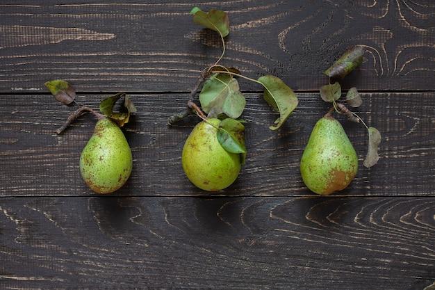 Poires vertes biologiques fraîches avec des feuilles au centre sur un fond en bois brun naturel