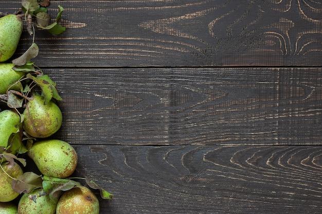 Poires vertes biologiques fraîches avec des feuilles sur un fond en bois brun naturel