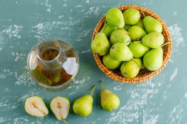 Poires vertes dans un panier avec du cidre à plat sur une table en plâtre