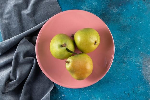 Poires vertes entières placées sur une assiette rose.