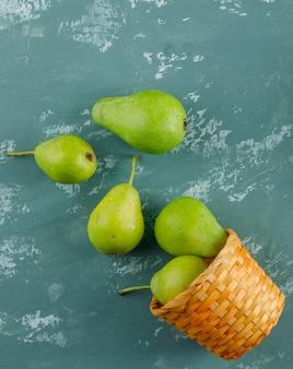 Poires vertes éparpillées dans un panier sur une surface en plâtre, à plat.