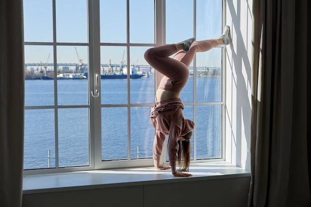 Le poirier sur le rebord de la fenêtre à la maison réalisé par une femme flexible en rose