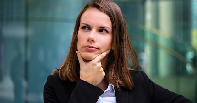 Poirtrait de femme d'affaires souriant dans une expression pensive