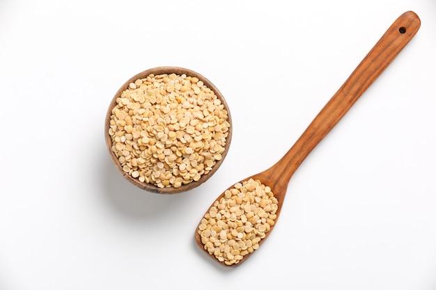 Pois d'angole non poli également connu sous le nom de toor dal dans un bol et une cuillère. isolé sur fond blanc.