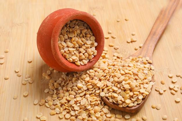 Pois d'angole non poli également connu sous le nom de toor dal dans un bol en métal. isolé sur fond en bois.