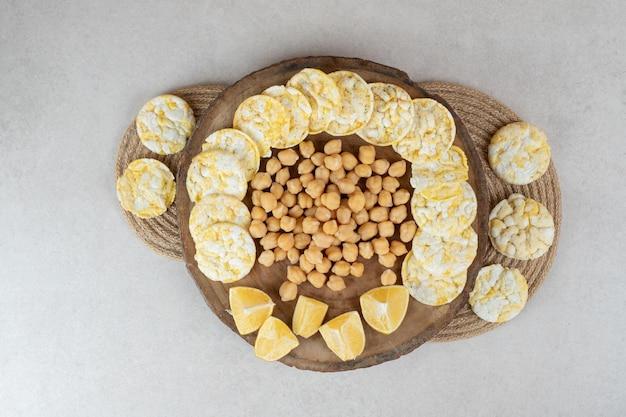 Pois bouillis, gâteaux de riz et citrons sur pièce en bois
