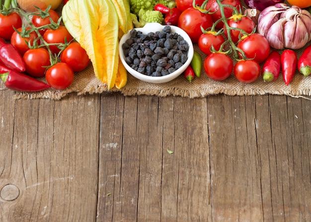 Pois chiche noir dans un bol de légumes crus sur une table en bois se bouchent avec copie espace