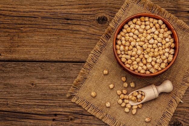 Pois chiche sec dans un bol en céramique sur une vieille table en bois. ingrédient traditionnel pour la cuisson du houmous