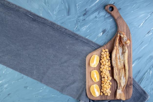 Pois chiches, citron tranché et poisson séché sur une planche à découper sur un torchon, sur fond bleu.