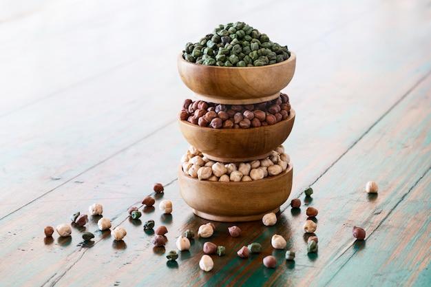 Pois chiches colorés (rouge, vert, blanc) dans des bols en bois sur fond rustique.