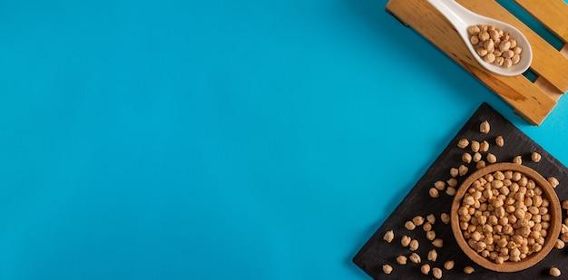 Pois chiches dans un bol en liège et surface en ardoise avec une cuillère en porcelaine sur fond bleu espace de copie