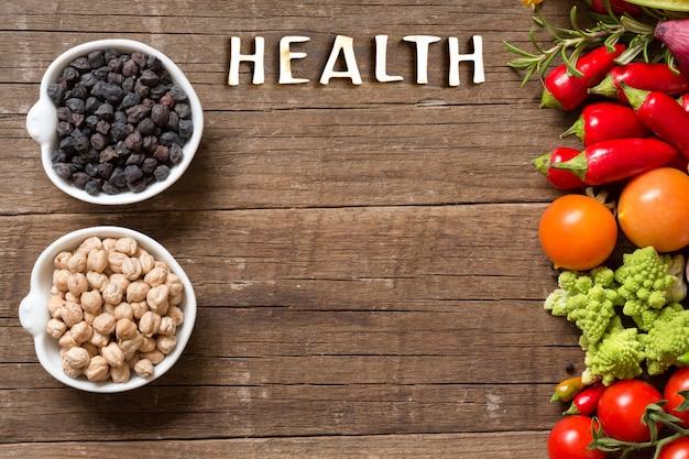 Pois chiches dans des bols avec des légumes et mot santé sur une table en bois avec copie espace vue de dessus