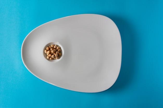 Pois chiches dans un plat élégant et minimaliste. mise à plat. espace de copie.