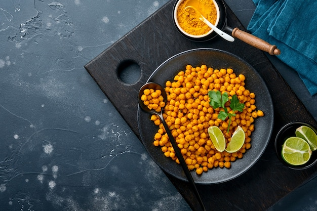 Pois chiches frits au curcuma avec persil et citron vert en plaque noire sur un vieux fond de tableau noir. pois chiches épicés rôtis ou chana ou chole indien, recette de collation populaire. vue de dessus.