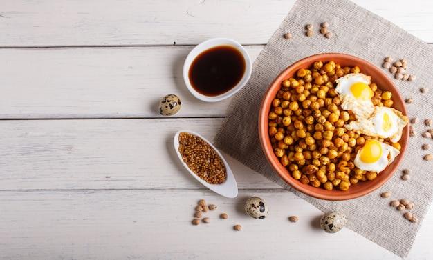 Pois chiches frits avec des oeufs de caille et des épices dans une assiette d'argile sur une surface en bois blanche.