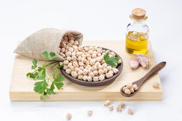 Pois chiches renversés sur une plaque en bois, huile d'olive, ail et persil.