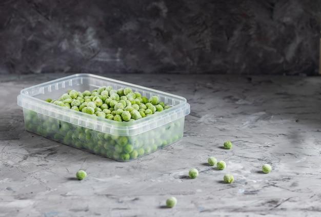 Pois verts congelés dans un récipient en plastique transparent