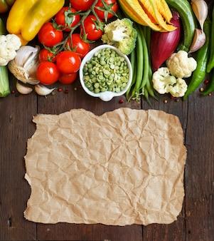 Pois verts dans un bol avec des légumes frais avec du papier kraft sur bois vue de dessus