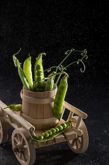 Pois verts frais dans un bol en bois, récolte de légumes