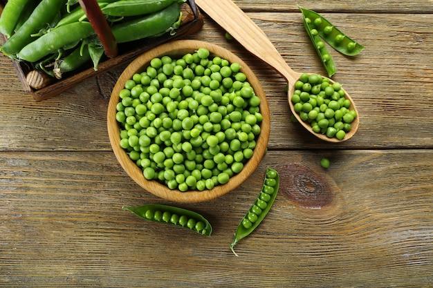 Pois verts frais dans un bol et une cuillère sur la table se bouchent