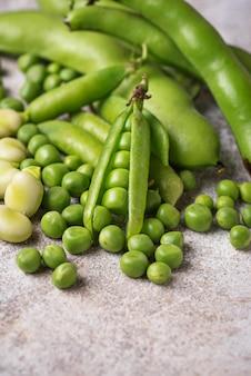 Pois verts frais et haricots sur fond clair